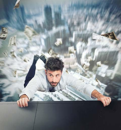 Crisis communications can prevent business disasters. Businessman hanging on a ledge.