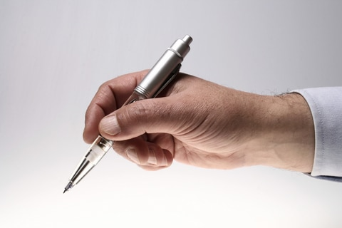 This ballpoint pen in a man's hand symbolizes the manuscript writing and editing process.
