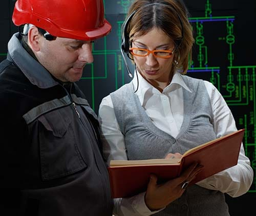 Engineer & assistant reviewing an instruction manual.