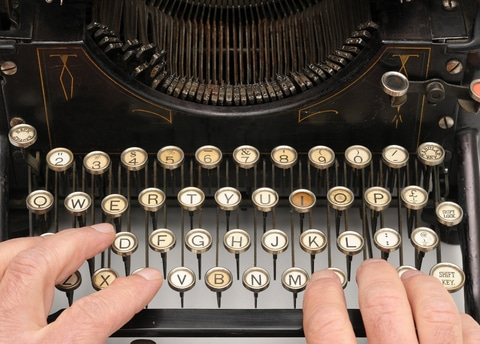 Writing a book with a ghostwriter will involve putting hands on a keyboard, although not actually a typewriter, as in this photo.