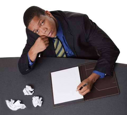 Clearly, this man at a desk with cumpled papers needs to find a ghostwriter. Hire us! :)